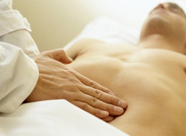 Мужчине с больным животом делают лечебный массаж